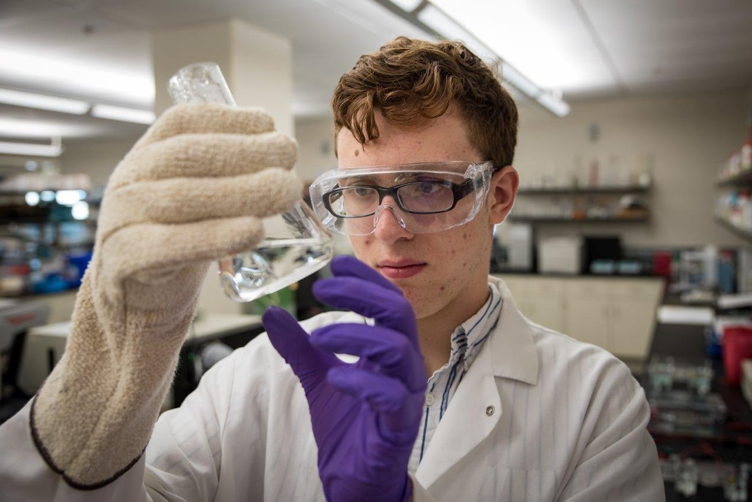 Peter Menart, member of the Air Force Research Laboratory-Carroll High School iGEM team, examines liquid in a beaker during the laboratory phase of the team's project prior to the iGEM competition in Boston.  (U.S. Air Force photo/Richard Eldridge)