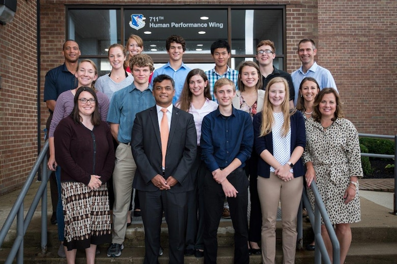 Members of the Air Force Research Laboratory-Carroll High School iGEM team stand with their CHS teachers and AFRL mentors in front of the 711th Human Performance Wing headquarters building following a presentation given to the 711HPW Chief Scientist Dr. Rajesh Naik (front, second from left).  (U.S. Air Force photo/Richard Eldridge)