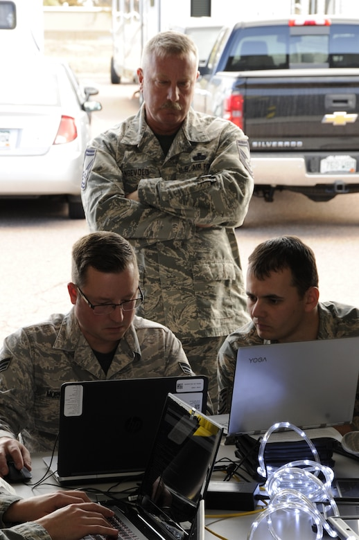 "Senior Master Sgt. Robbie Engevold, the 302nd Communications Flight superintendent, looks on as Senior Airman Stephen Morrison, left, a 302nd CF cyber operations technician,  , and Tech. Sgt. Raymond Shaw, NCO in charge of cyber transport technicians, take on a coding challenge during a ""Capture the Flag"" cyber operations challenge at Peterson Air Force Base, Colo., Nov. 4, 2017. Members of the 302nd Communications Flight took part in the ""Capture the Flag"" cyber operations challenge during the November Unit Training Assembly, which aimed to test their ability to identify and respond to cyber threats in a simulated environment.. (U.S. Air Force photo/1st Lt. Stephen J. Collier)"