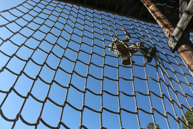 A soldier climbs a cargo net against a backdrop of blue sky.