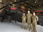 Army Pfc. Ashley Goss of Navarre, Fla.; Chief Warrant Officer 3 Tyson Edkin of Kansas City, Mo.; and Staff Sgt. Aaron Dunn of Long Beach, Calif.; with the 4-6 Attack Cavalry Squadron, 16th Combat Aviation Brigade are seen in front of an AH-64 Apache attack helicopter, at the squadron's hangar at Joint Base Lewis-McChord, Washington, Nov. 14, 2017. DoD photo by Lisa Ferdinando