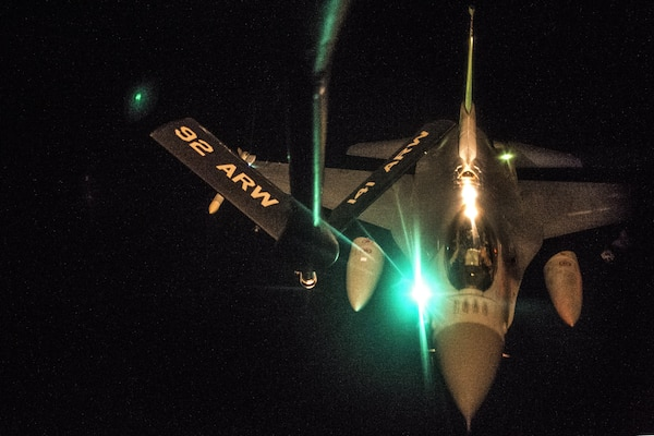 An aircraft receives fuel at night in flight.