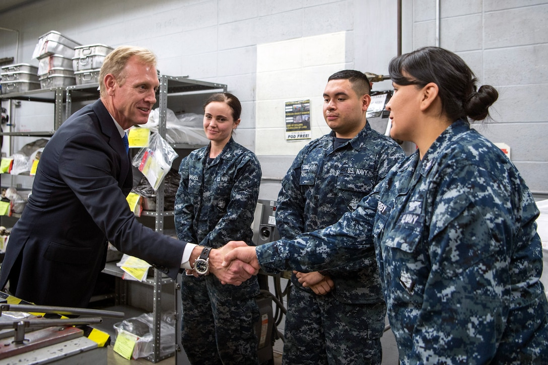 Deputy Defense Secretary Pat Shanahan shakes hands with a sailor as two other sailors look on.