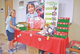 Nine-year-old Hannah Malmquist, daughter of John Malmquist, community director for Club Beyond at Fort Riley, places a completed shoebox gift on the Operation Christmas Child donation table Oct. 20 at Victory Chapel. Community members fill shoeboxes with items to be shipped to children in need in third world countries, John said. The boxes are delivered to the children in late December.