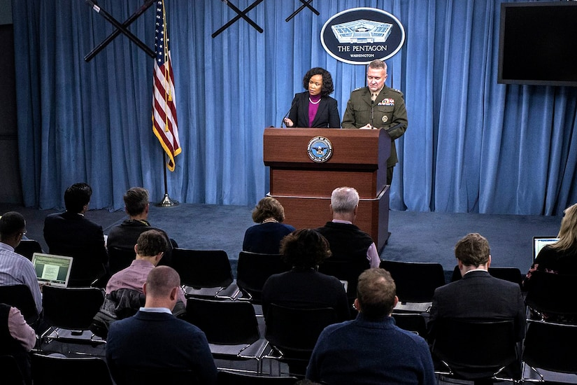 Two Pentagon officials speak from a podium at a news conference.