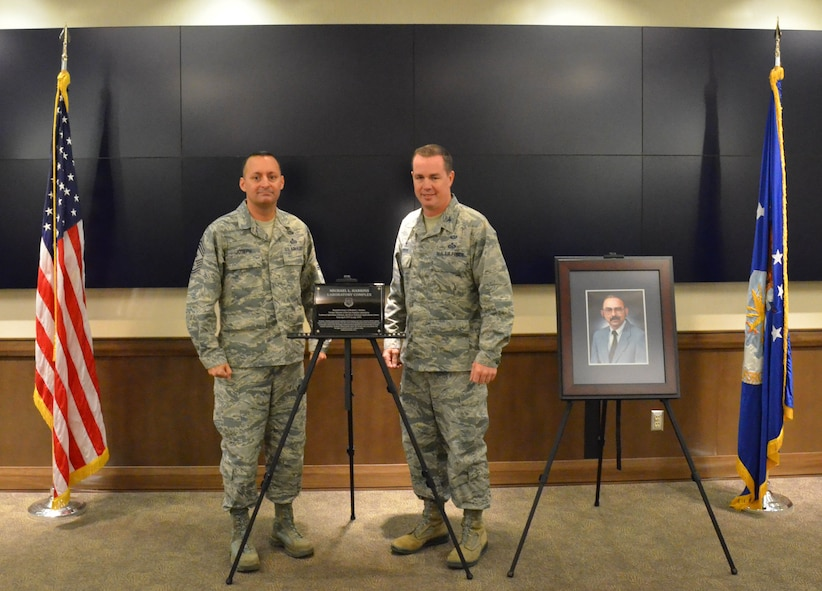 Col. Steven M. Gorski (right), commander of the Air Force Technical Applications Center, and Chief Master Sgt. Michael Joseph, AFTAC's command chief, pose next to the plaque that officially dedicates the center's research laboratory after former AFTAC senior scientist, Michael Harkins, at a ceremony at Cheyenne Mountain Air Force Station, Colo.  Harkins' official portrait is on the right.  (U.S. Air Force photo by Susan A. Romano)