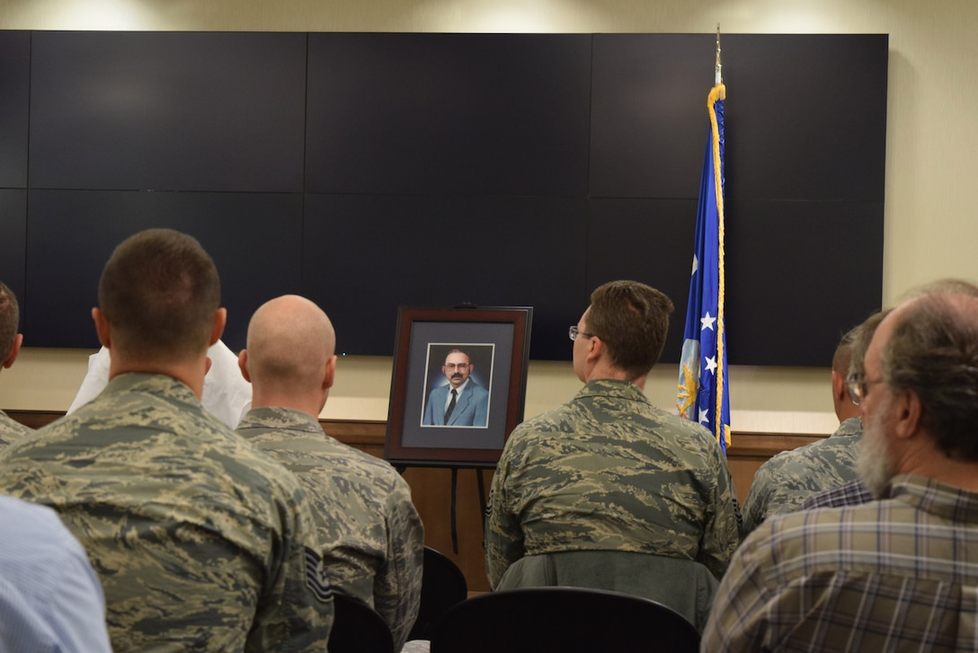 Members of the Harkins Laboratory Complex at Cheyenne Mountain Air Force Station, Colo., listen to remarks from Col. Steven M. Gorski, commander of the Air Force Technical Applications Center, during the dedication ceremony that named the lab after Michael Harkins, a former AFTAC senior scientist.  Harkins' official portrait is seen in the center of photo.  (U.S. Air Force photo by Susan A. Romano)
