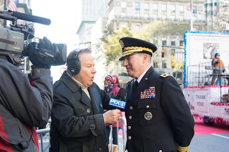 (Right) Maj. Gen. Mark W. Palzer, commander of the 79th Theater Sustainment Command, represented the U.S. Army and U.S. Army Reserve during an interview with (Center) Marvin Scott of WPIX-TV at the NYC Veterans Day Parade, November 11, 2017. (U.S. Army Reserve Photo by Maj. Addie Leonhardt, 80th Training Command)
