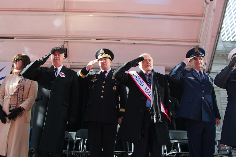 (Left to Right) Mrs. Donna Wartski; Mr. Jim Wartski; Army Reserve Maj. Gen. Mark Palzer, commander of the 79th Theater Sustainment Command; Mr. Buzz Aldrin, Grand Marshall; and Air Force Maj. Ronald Franco salute the 77th Sustainment Brigade and 80th Training Command Soldiers marching past the review stand at the NYC Veterans Day Parade, November 11, 2017. (U.S. Army Reserve Photo by Maj. Addie Leonhardt, 80th Training Command).