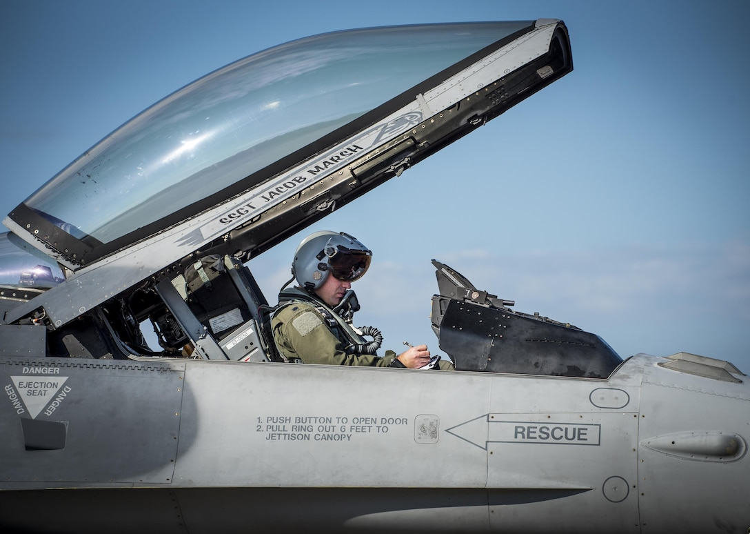 A 55th Fighter Squadron pilot from Shaw Air Force Base, S.C., makes notes in his F-16 Fighting Falcon prior to a Combat Hammer sortie Nov. 2, at Eglin AFB, Fla.  A-10s, F-16s, F-22s and MQ-9s visited the base to participate in the 53rd Wing exercise. The 86th Fighter Weapons Squadron's Combat Hammer is a weapons system evaluation program for air-to-ground munitions. (U.S. Air Force photo/Samuel King Jr.)