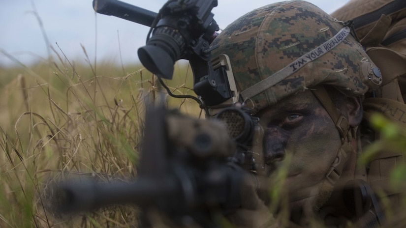 A Marine provides security while participating a simulated night raid during an air assault training event at Marine Corps Air Station Futenma, Okinawa.