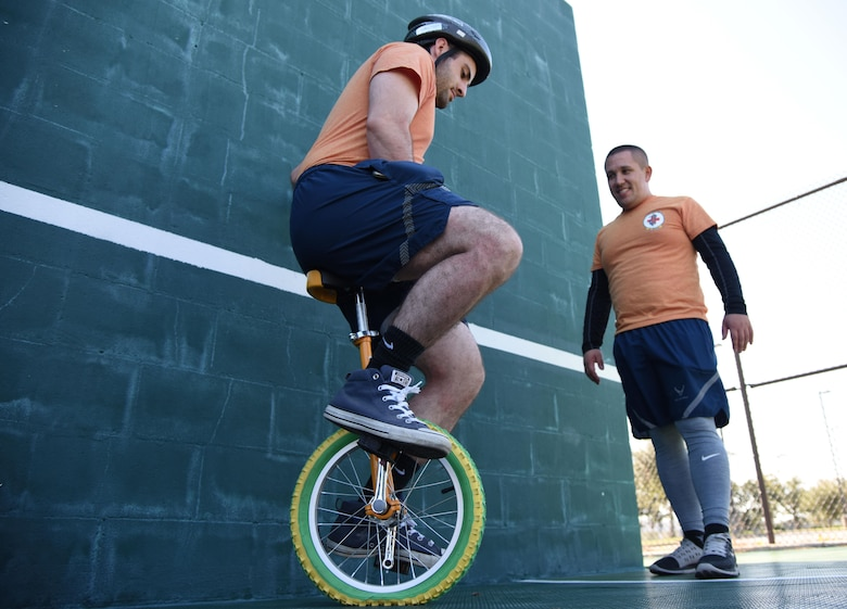 Senior Airmen Emanuel De Alba, 81st Medical Support Squadron professional contracting officer representative, and Angel Tucker, 81st MDSS medical logistics technician, participate in an unicycle training class during Wingman Day Nov. 16, 2017, on Keesler Air Force Base, Mississippi. Wingman Day consisted of Keesler Airmen participating in unit-wide Comprehensive Airman Fitness courses which focused on resiliency and teambuilding initiatives across the base. (U.S. Air Force photo by Kemberly Groue)
