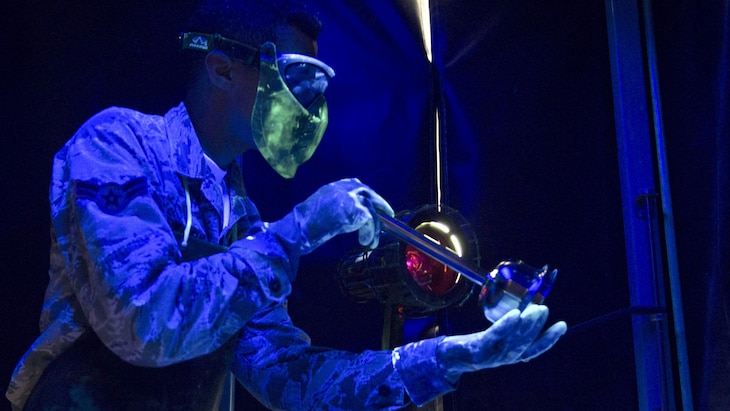 An airman wearing goggles and gloves inspects an item, against a deep blue background.