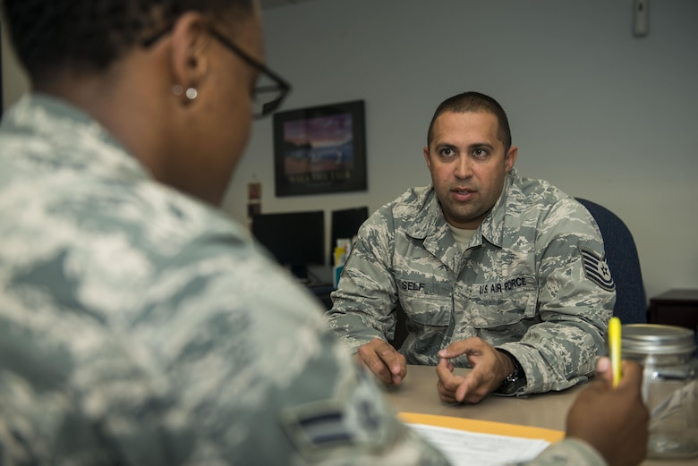 U.S. Air Force Airman 1st Class Lakeia Garner, 20th Force Support Squadron outbound assignments personnel specialist, left, speaks with Tech. Sgt. William Self, 20th Aircraft Maintenance Squadron lead engine technician, about his orders at Shaw Air Force Base, South Carolina, Nov. 13, 2017.