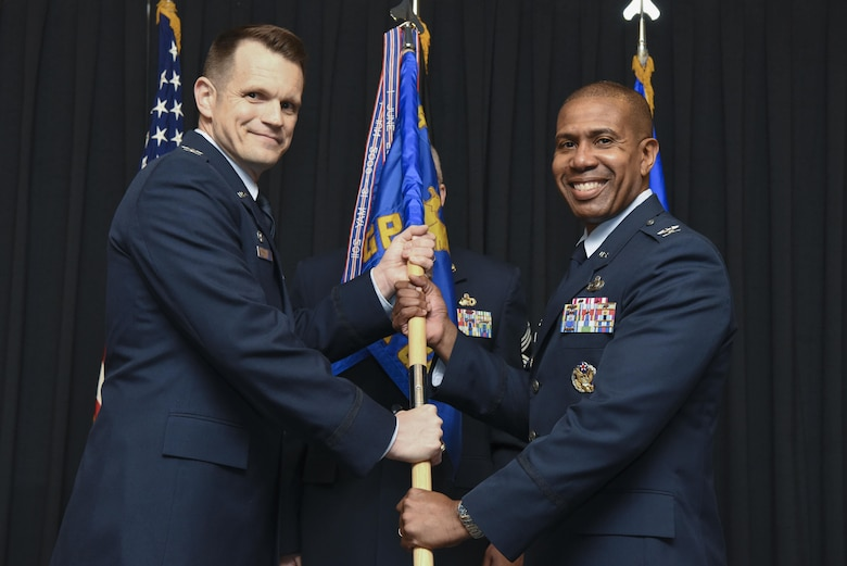 U.S. Air Force Col. Jason Brown, 480th Intelligence, Surveillance and Reconnaissance Wing commander, passes the guidon to Col. Tracy Ward, 693rd ISR Group commander, during the Assumption of Command ceremony Nov. 15, 2017, at Ramstein Air Base, Germany.