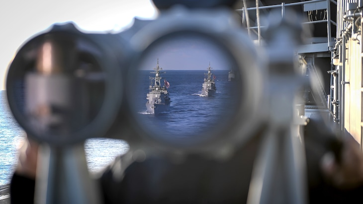 Two ships in the ocean are visible in a binocular lens aboard a ship.