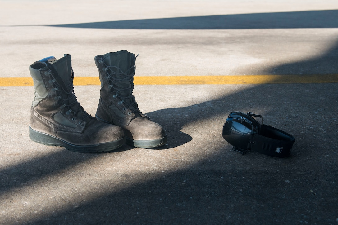 A pair of boots and hearing-protective earphones lie on the ground after being set aside by an Airman prior to climbing into the intake of an F-16CM Fighting Falcon at Shaw Air Force Base, South Carolina, Nov. 16, 2017.
