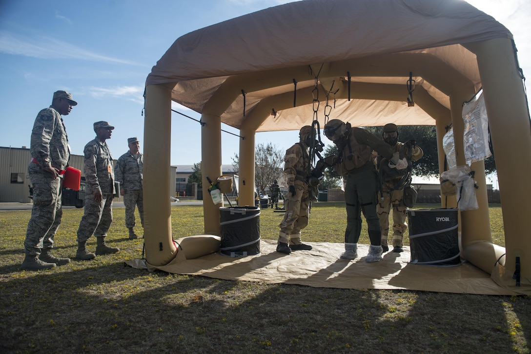 U.S. Airmen simulate decontaminating a pilot while wing inspection team members watch during the first Rapid Ready Weasel at Shaw Air Force Base, South Carolina, Nov. 16, 2017.