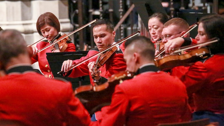 Marines in red uniforms play violins inside a cathedral.