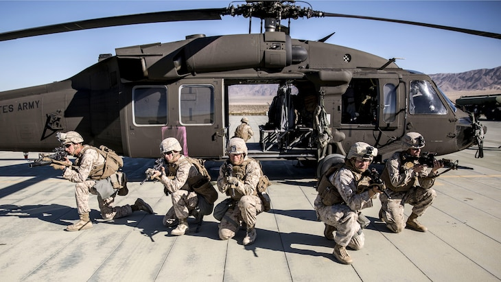 Marines kneel and point weapons while fanned out in front of a helicopter.