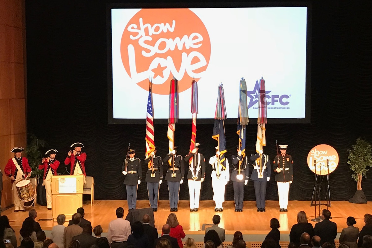 Service Members display flags on stage.