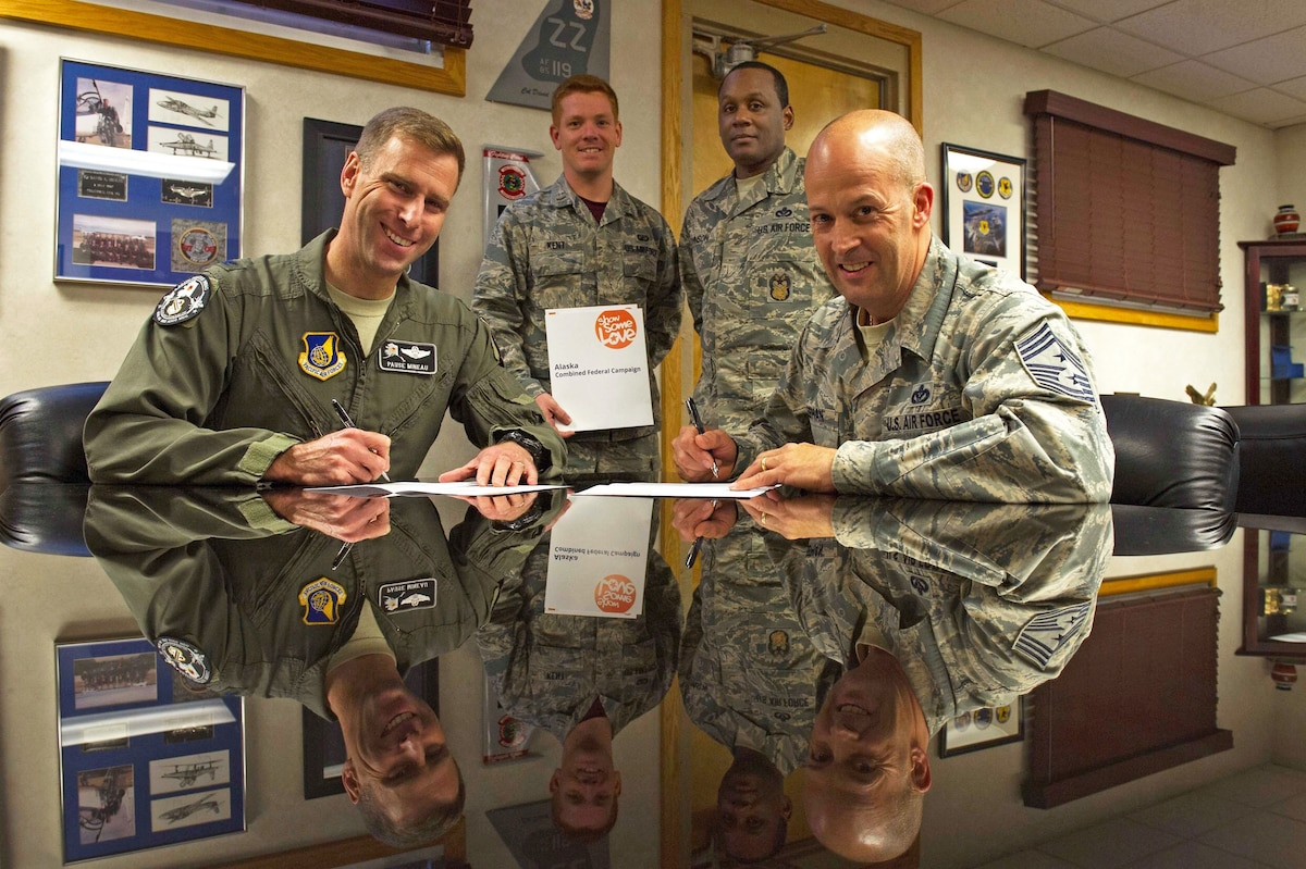 Two airmen sit at a table while two others stand in the background.