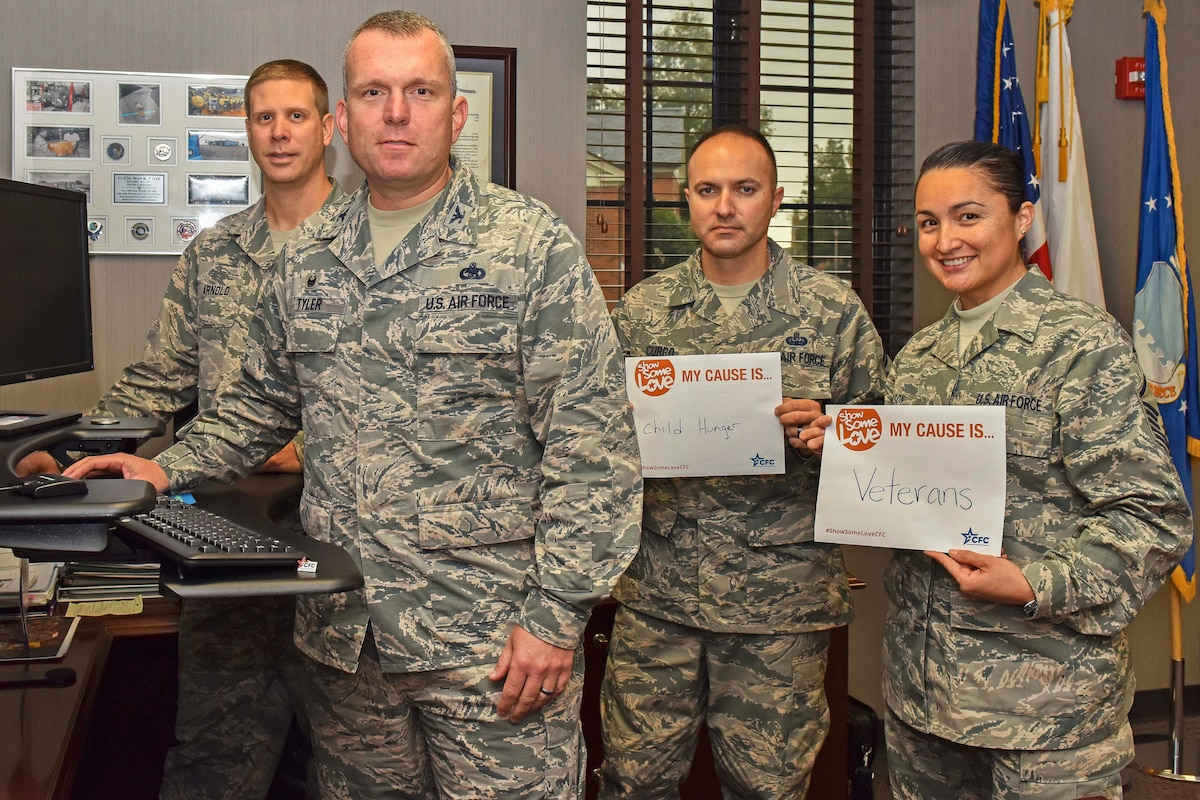 Four airmen stand while posing for a photo.