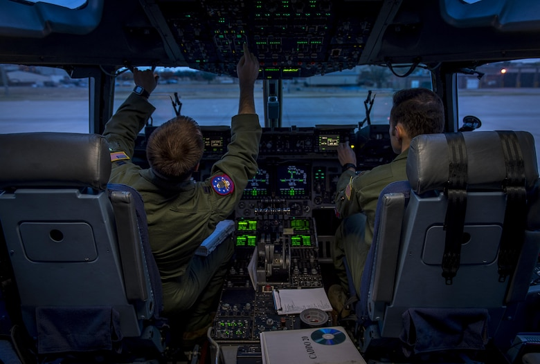 U.S. Air Force Capt. Eric Miller, an instructor pilot with the 97th Training Squadron and Maj. Chris Black, an instructor pilot with the 58th Airlift Squadron, perform pre-flight checks in a C-17 Globemaster III during the Altus Quarterly Exercise (ALTEX), Nov. 16, 2017 at Altus Air Force Base, Okla.