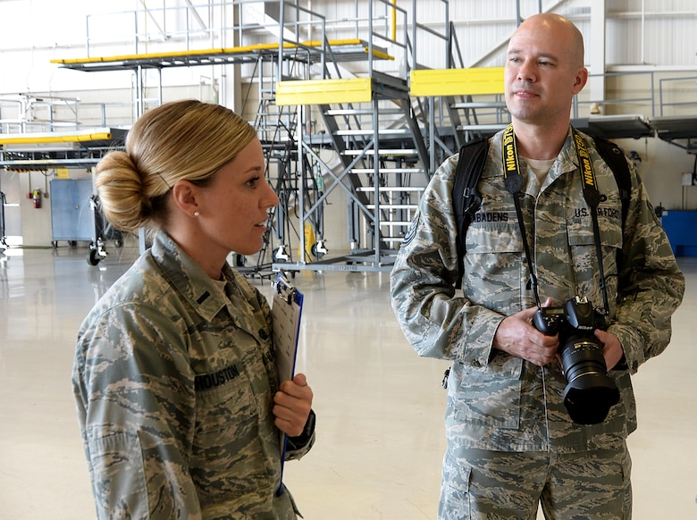 First Lt. Brianna Houston, 81st Training Wing Protocol Office chief of protocol, speaks to Tech. Sgt. Ryan Labadens, 403rd Wing Public Affairs photojournalist, about photos she is requesting of the 22nd Air Force change of command in the isochronal dock Nov. 14, 2017, on Keesler Air Force Base, Mississippi. The Protocol Office is in charge of ensuring every ceremony on Keesler goes to plan according to Air Force standards. (U.S. Air Force photo by Airman 1st Class Suzanna Plotnikov)