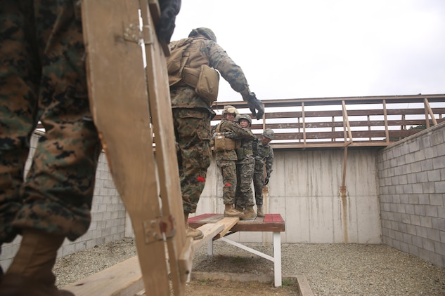 U.S. Marines with Landing Support Company, 3rd Transportation Support Battalion, Combat Logistics Regiment 3, cross an obstacle with help from Republic of Korea Marines with Landing Support Battalion, ROK Marine Logistics Group, Oct. 28, 2017 at ROK MLG Base, Pohang, South Korea. The Marines from both nations came together to conduct a Leadership Reaction Course, a series of team-building exercises designed to encourage communication and camaraderie between the two forces. The LRC was held as a part of Exercise Winter Workhorse 17/ Korean Marine Exchange Program 18.1, which builds individual Marines and Sailors' relationships with their ROK counterparts and is the strength of III MEF in the Pacific. (U.S. Marine Corps photo by Sgt. Tiffany Edwards)