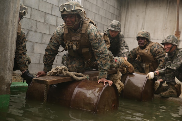 Lance Cpl. Larry Anderson, a landing support specialist with Landing Support Company, 3rd Transportation Support Battalion, Combat Logistics Regiment 3, crosses an obstacle with help from his unit and Republic of Korea Marines with Landing Support Battalion, ROK Marine Logistics Group, Oct. 28, 2017 at ROK MLG Base, Pohang, South Korea. The Marines from both nations came together to conduct a Leadership Reaction Course, a series of team-building exercises designed to encourage communication and camaraderie between the two forces. The LRC was held as a part of Exercise Winter Workhorse 17/ Korean Marine Exchange Program 18.1, which builds individual Marines and Sailors' relationships with their ROK counterparts and is the strength of III MEF in the Pacific. (U.S. Marine Corps photo by Sgt. Tiffany Edwards)