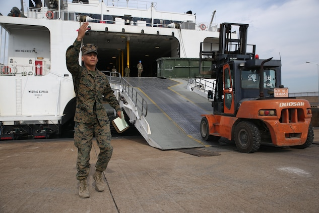 Lance Cpl. Antonio Diaz, a logistics embarkation specialist with Headquarters Company, Combat Logistics Regiment 3, directs forklifts with cargo onto a high-speed vessel, Nov. 13, 2017 at Pohang Port, South Korea. CLR-3 successfully completed a month-long deployment to South Korea for Exercise Winter Workhorse 17/ Korean Marine Exchange Program 18.1, which familiarizes the American armed forces with the Korean Peninsula and builds upon an enduring alliance between the two militaries. (U.S. Marine Corps photo by Sgt. Tiffany Edwards)