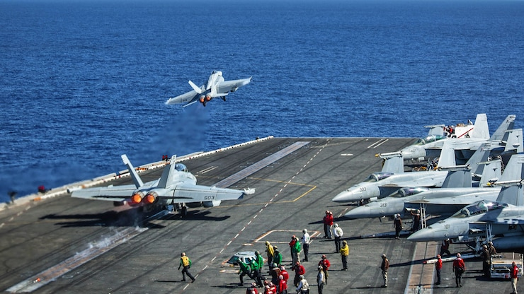 Two aircraft take off from the flight deck of an aircraft carrier.