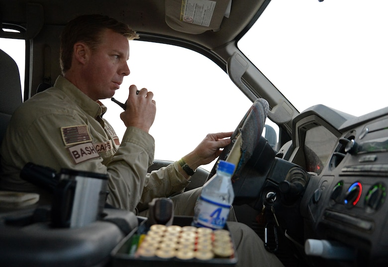 James Capps, 455th Air Expeditionary Wing U.S. Department of Agriculture (APHIS) and BASH forward operating base biologist, radios in to the air traffic control tower before crossing the runway Nov. 21, 2017 at Bagram Airfield, Afghanistan.
