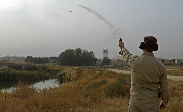 James Capps, 455th Air Expeditionary Wing U.S. Department of Agriculture (APHIS) and BASH forward operating base biologist, shoots off a pyrotechnic to harass wildlife off of Coyote Creek, Nov. 21, 2017 at Bagram Airfield, Afghanistan.