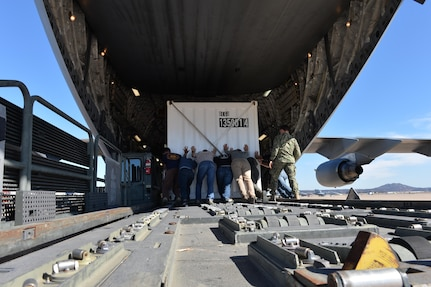 People push a container onto a cargo plane.
