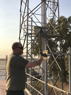 Air Force Tech. Sgt. Clayton Allen, 22nd Air Refueling Wing, installs a communications antenna at Moron Air Base, Spain, Oct. 10, 2017. Allen is a water and fuels systems maintenance technician who's self-taught in computer programming and satellite and ground command-and-control radio systems. Air Force photo by Senior Airman Jenna Caldwell