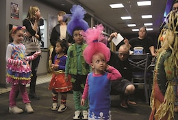 "Kids ages 5 years old and younger dressed in Halloween costumes wait with their parents for the best-dressed winner to be announced during the Custer Hill Bowling Alley costume party Oct. 28. The prize was shared between siblings Traesin Wright, 5, son of Spc. Dylan Waide, 258th Human Resources Company, 1st Inf. Div. Sustainment Brigade; who dressed as Branch from ""Trolls,"" and his sister Mahlea Waide, 2, who dressed as Poppy from the same movie."