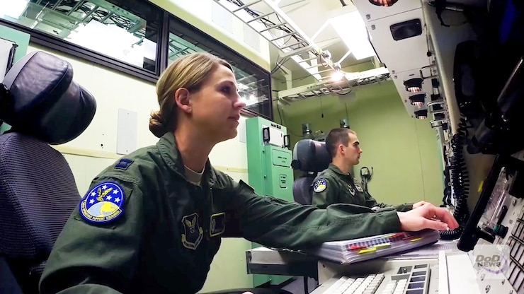 Service members work in a control room.