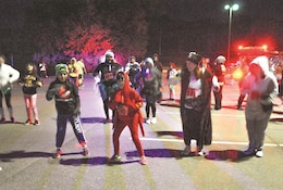 Costumed runners dance before the start of the GLO Run Oct. 27 that began at Sacco Softball Complex. There were two routes for the run. One was a 1.4-mile candy parade for children and the other was a 5 kilometer run around Moon Lake.