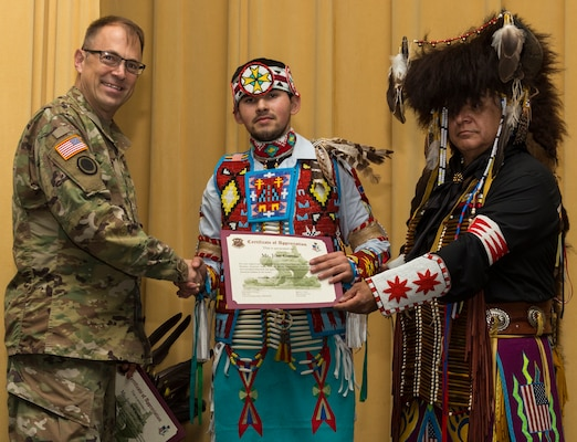 Jose Garcia II (center), a member of the American Indians in Texas Dance Theater group, receives a certificate of appreciation from Maj. Gen. Brian Lein, U.S. Army Medical Department Center and School commanding general (left), during the National American Indian Heritage Month Observance Nov. 16 at AMEDDC&S, located at Joint Base San Antonio-Fort Sam Houston. Standing to the right of Garcia is Isaac Cardenas, also a member of the American Indians in Texas Dance Theater group.