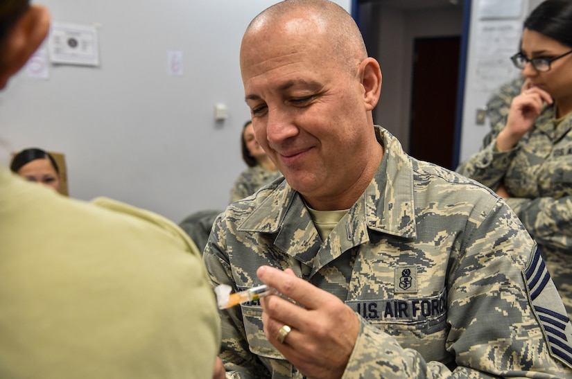 Chief Master Sgt. Joseph Powell, 628th Medical Group command chief, administers flu vaccines to base members during a during a mass-immunization exercise at Joint Base Charleston, S.C., Nov. 15, 2017.