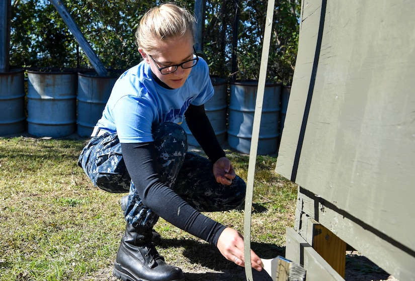 Lt. Junior Grade Erynn Schroeder, Naval Nuclear Power Training Command instructor, paints a Vietnam memorial exhibit during Day of Caring at Patriot's Point, Mount Pleasant, S.C., Nov. 17, 2017.