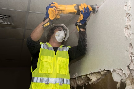 A member of the 502nd Civil Engineering Squadron cuts through a sheetrock wall during building renovations Nov. 18, 2017 at Joint Base San Antonio-Lackland. Forty office personnel from 502nd CES volunteered their weekend to help with renovations to meet a short deadline.