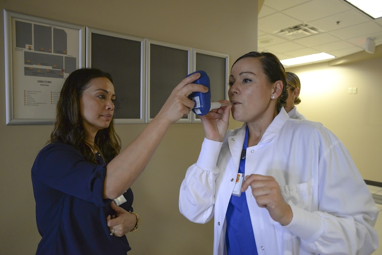 Yyolany Caffrey, 56th Medical Group Health Promotions coordinator, performs a carbon monoxide test on Airman 1st Class Amanda Giovannoni, 56th Medical Group dental assistant, at Luke Air Force Base, Ariz., Nov. 17, 2017. The test was used to compare lung function of non-smokers versus smokers. (U.S. Air Force photo/Airman 1st Class Caleb Worpel)