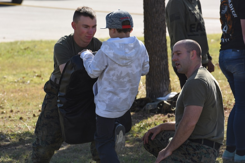 U.S. Marine Pfc. Stephn Dorn, Marine Corps Detachment at Goodfellow Air Force Base trainee, holds a pad while Staff Sgt. Calvin Bradbury, MCD instructor, teaches self-defense to a child during the Santa's Market and Community Appreciation Day at the Louis F. Garland Department of Defense Fire Academy on Goodfellow Air Force Base, Texas, Nov. 18, 2017. The MCD offered hand-to-hand lessons to anyone interested and provided step-by-step guidance on each exercise. (U.S Air Force photo by Airman 1st Class Zachary Chapman/Released)
