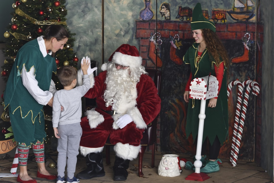 Santa Clause high-fives a child before asking him what he wants for Christmas at the Santa's Market and Community Appreciation Day at the Louis F. Garland Department of Defense Fire Academy on Goodfellow Air Force Base, Texas, Nov. 18, 2017. Children were invited to sit on Santa's lap and pose for a photo after giving him their list of toys they wanted. (U.S Air Force photo by Airman 1st Class Zachary Chapman/Released)