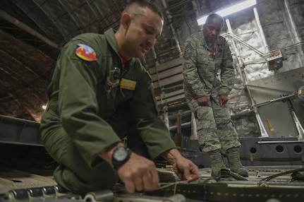 Tech. Sgt. Mitchell Thompson, 15th Airlift Squadron loadmaster flight chief of training, demonstrates how to secure an extraction line bag to the ramp of a C-17 Globemaster III for aircrew members and Chief Master Sgt. Shelina Frey, Air Mobility Command command chief, on a C-17 on the flightline in Joint Base Charleston, S.C., Nov. 17, 2017.