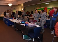 90th Medical Group Airmen wait for patrons to come to the Warren Top 3 craft fair and health fair, to share their information on F.E. Warren Air Force Base Wyo., Nov. 17, 2017. The purpose of the Fair is to promote health, wellness and safety to not only the base but community beneficiaries. Squadrons from all across the wing and people from the community set up booths to help promote health, safety or sell their crafts. (U.S. Air Force photo by Airman 1st Braydon Williams)