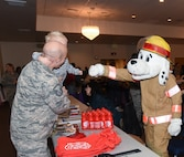 Sparky, the Fire Rescue mascot, fist bumps a child at the Warren Top 3 craft fair and health fair on F.E. Warren  Air Force Base Wyo., Nov. 17, 2017. Squadrons from all across the wing and members from the community set up booths to help promote health, safety or to just sell their crafts. (U.S. Air Force photo by Airman 1st Braydon Williams)